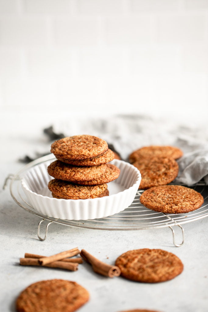 snickerdoodle cookies stacked in a dish on a wire rack